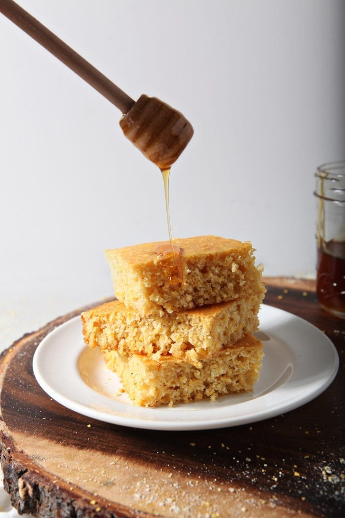 Honey drizzles on top of stacked, sliced cornbread