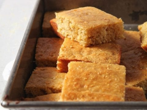 Homemade cornbread is stacked in a pan, sliced, before serving