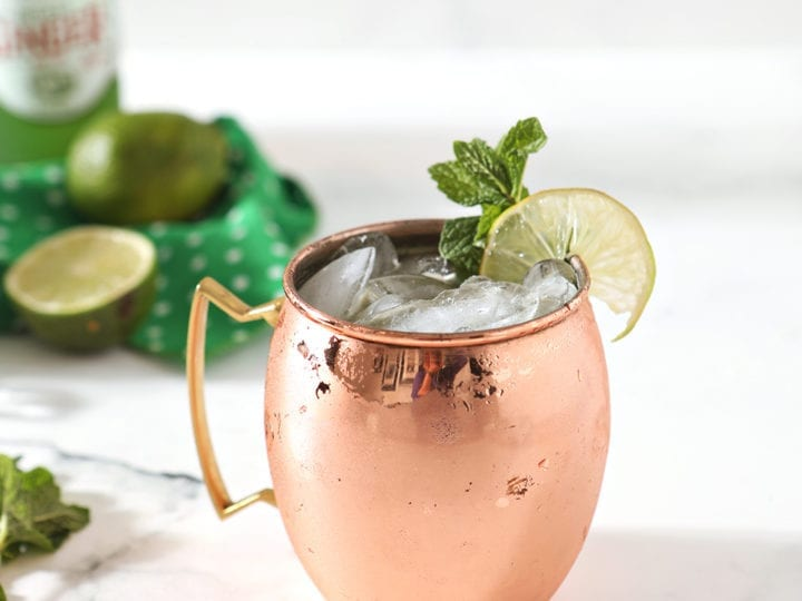 A copper mug holding an Irish Whiskey Moscow Mule sits on a marble background, surrounded by ingredients
