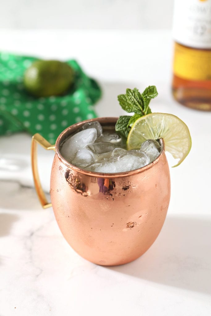 A copper mug holds an Irish Mule on a marble background, surrounded by ingredients