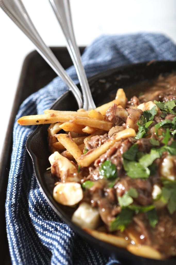 Close up of Beefy Poutine Fries and Gravy with forks in a skillet