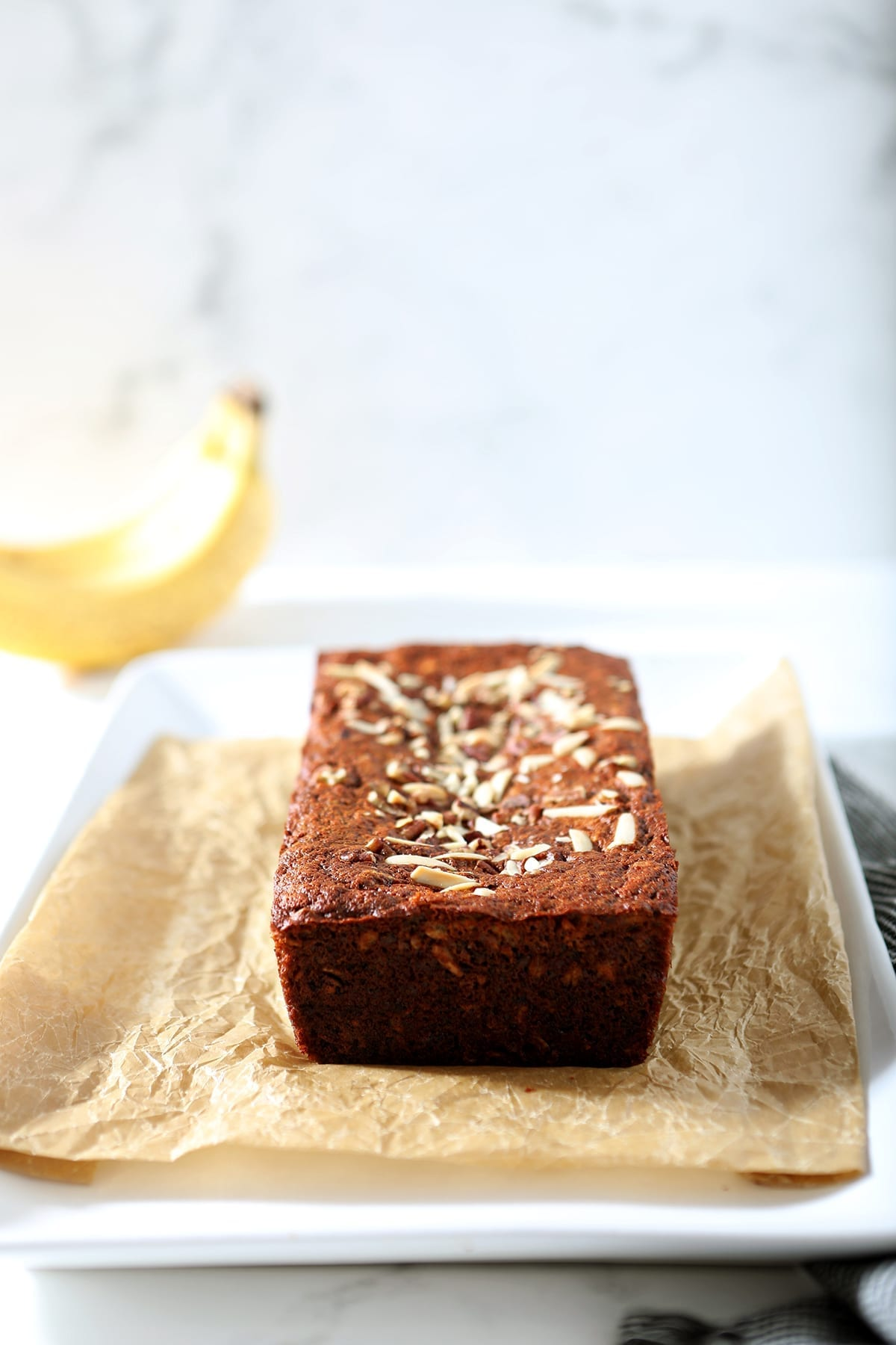 A loaf of Banana Bread sits on a piece of parchment paper on a white platter, ready for slicing