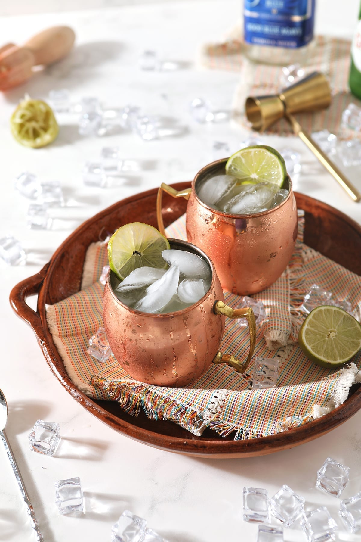 A brown tray holds two copper mugs of Mexican Mules, with ice and lime wedges around them