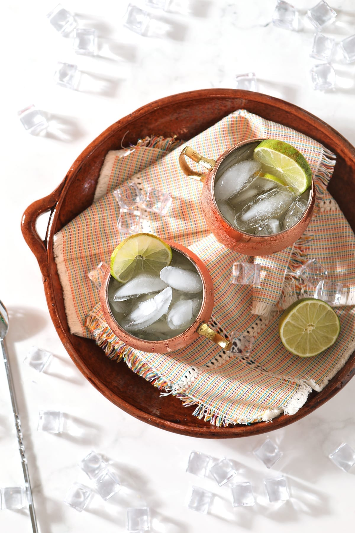 Overhead of a platter holding two Mexican Mules in copper mugs, with lime garnishes and ice