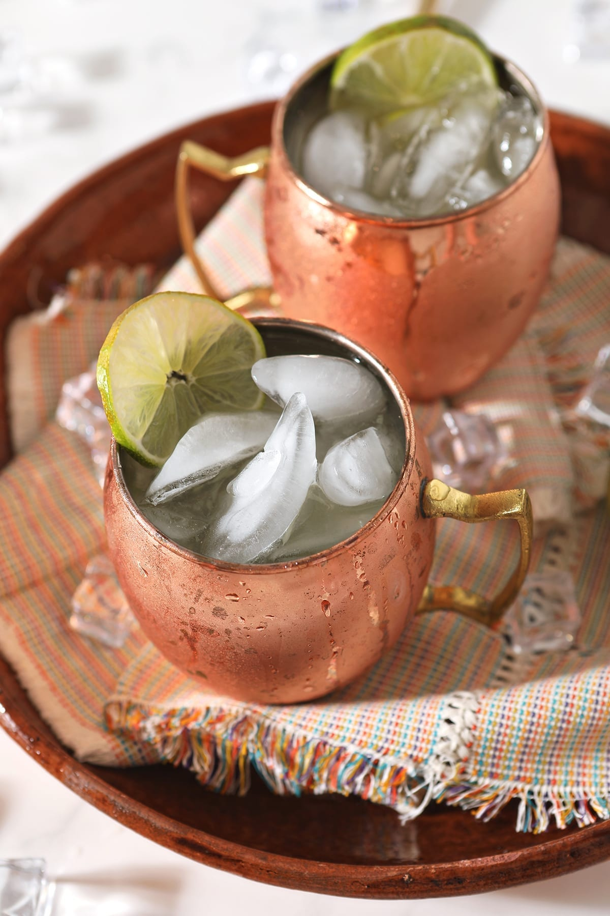 Overhead of two copper mule mugs holding liquor, on a platter