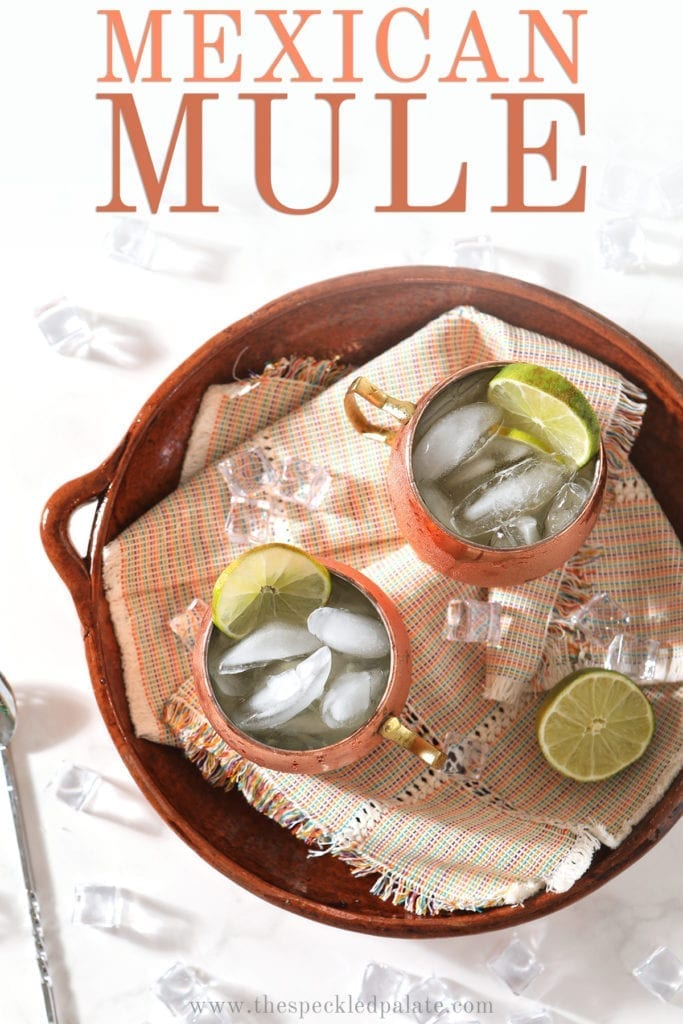 Overhead of two Moscow Mules on a brown platter, with Pinterest text