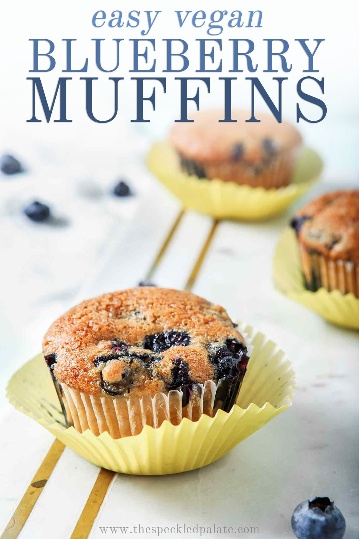 Three Vegan Blueberry Muffins on a marble slab, with Pinterest text