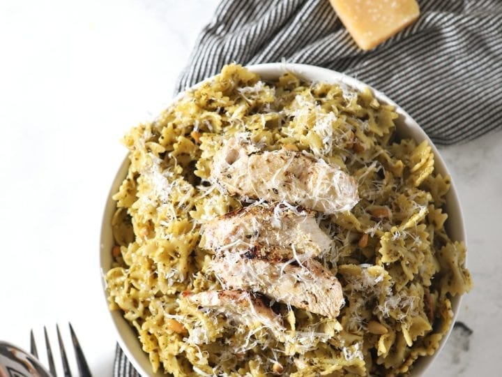 Overhead image of a white bowl holding Chicken Pesto Pasta, surrounded by ingredients