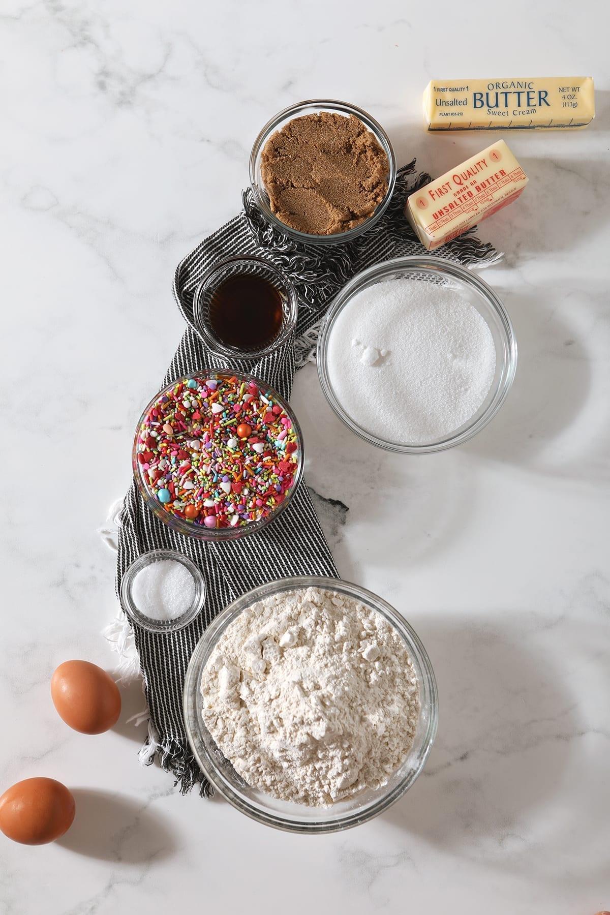 Flour, eggs, sprinkles, sugars, butter and more from above on a marble tabletop
