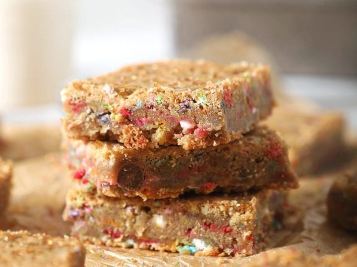 A stack of three cookie bars, shown on brown paper with other bars and in front of a glass of milk and a baking sheet
