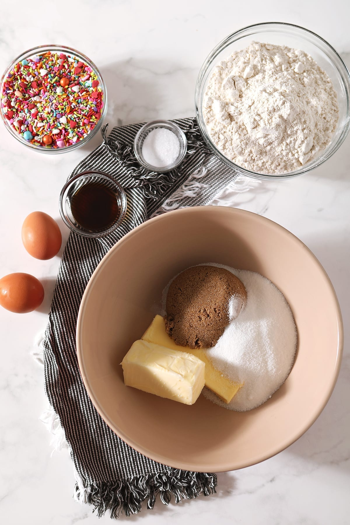 Sticks of butter and sugars are shown in a tan bowl, with eggs, vanilla and other ingredients around them