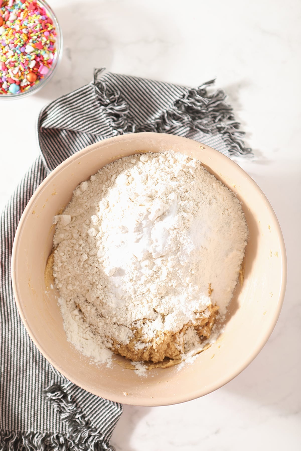 Flour is shown on top of other ingredients in a bowl