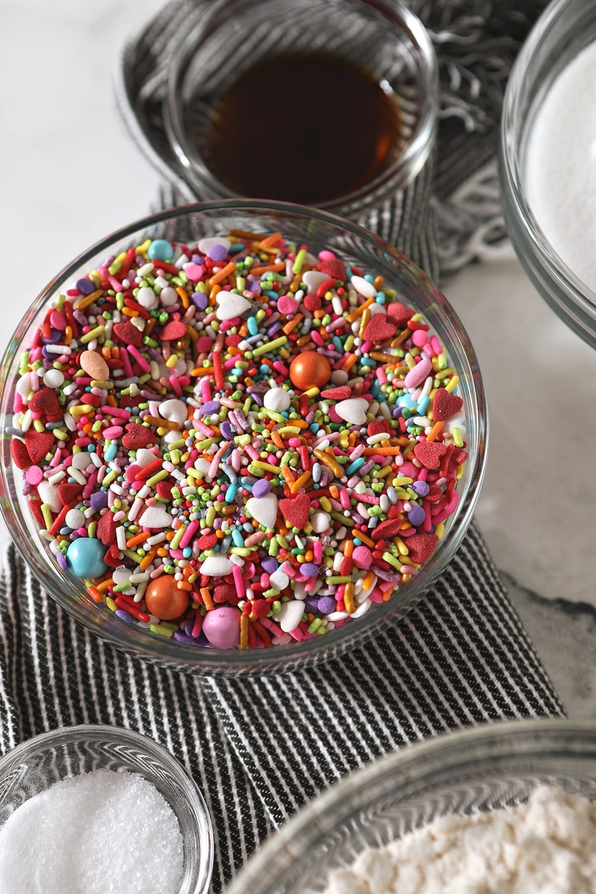 A bowl of colorful sprinkles, surrounded by other ingredients