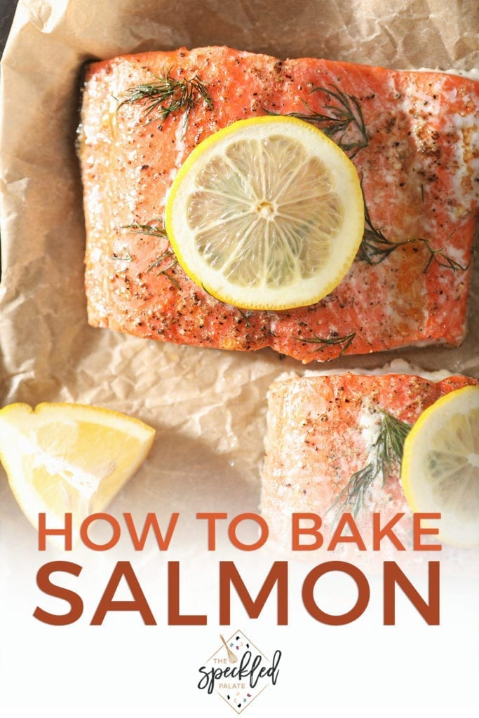 """Close up of baked salmon garnished with lemon rounds on parchment paper with Pinterest text stating, """"How to Bake Salmon"""""""