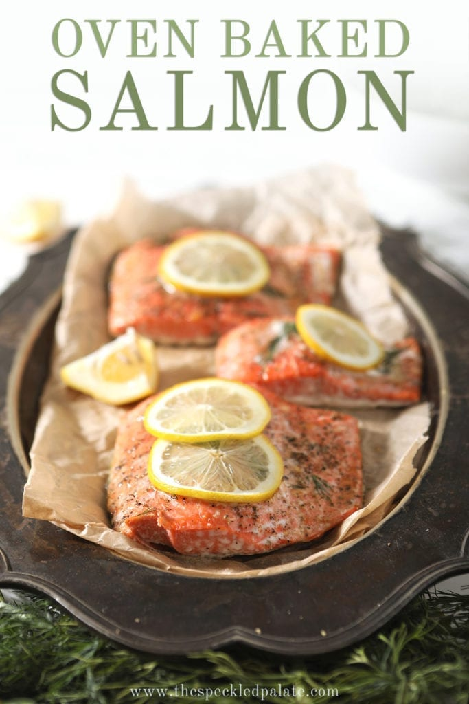 """Baked salmon on a silver platter with lemon rounds and fresh dill with Pinterest text stating, """"Oven Baked Salmon"""""""