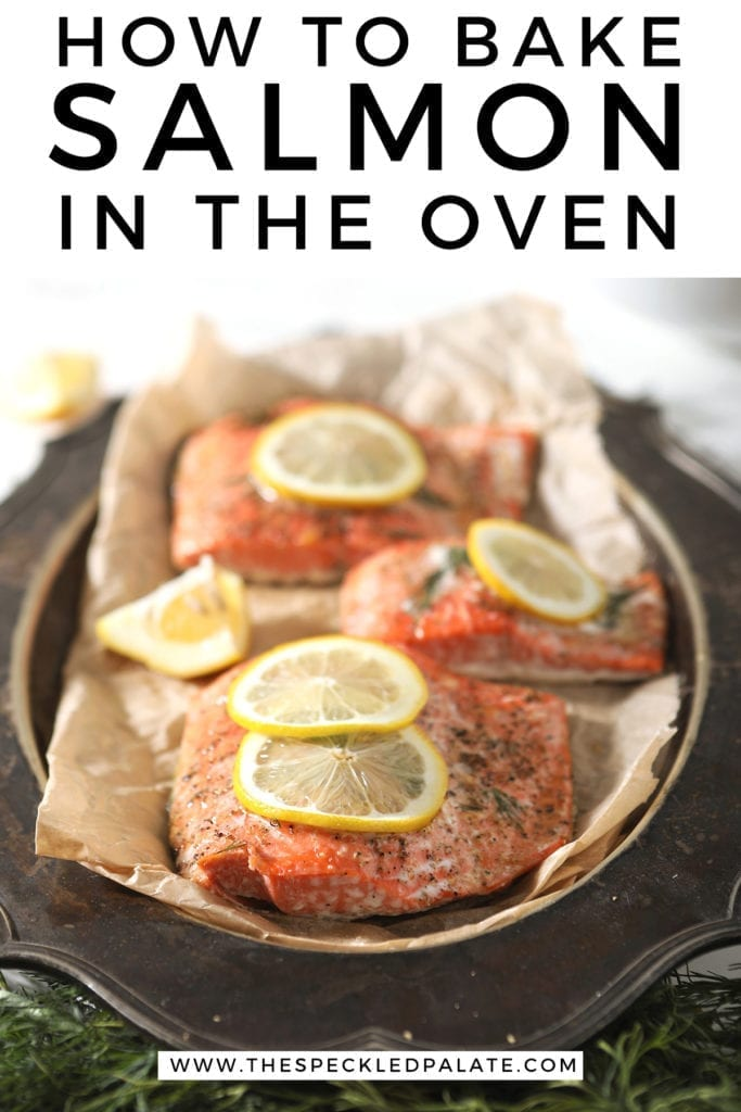 """Baked salmon garnished with lemon rounds on parchment paper on a silver platter with Pinterest text stating, """"How to Bake Salmon in the Oven"""""""