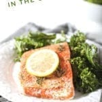 """A baked salmon filet with a lemon round on parchment paper on white plate with a kale salad and Pinterest text stating, """"How to Bake Salmon in the Oven"""""""