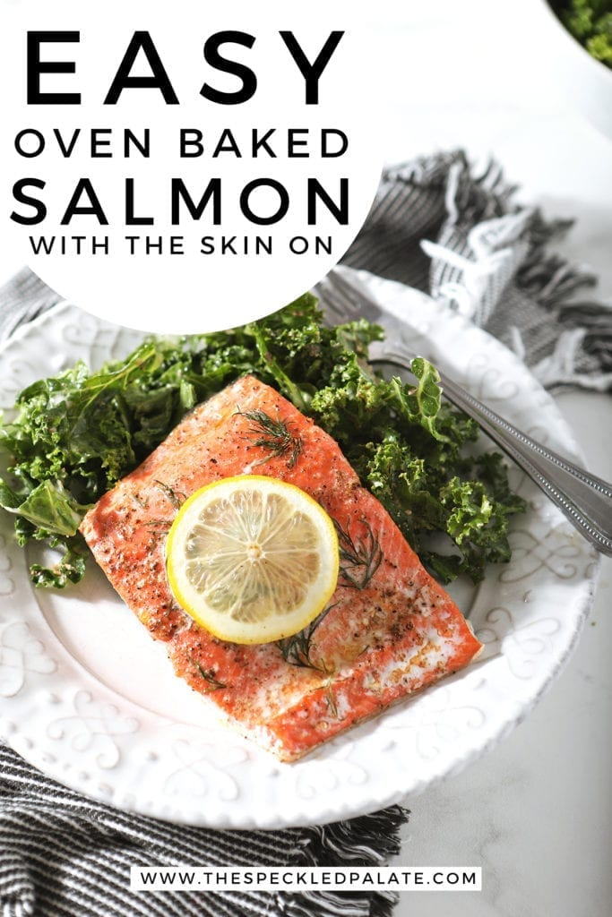 """A baked salmon filet with a lemon round on a white plate with a kale salad and Pinterest text stating, """"Easy Oven Baked Salmon with the Skin On"""""""