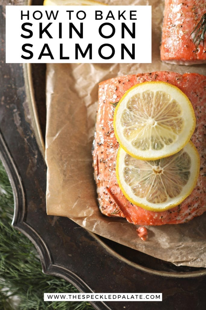 """Close up of a baked salmon filet with a lemon round on parchment on a silver platter with Pinterest text stating, """"How to bake skin on salmon"""""""