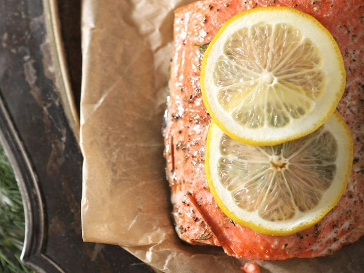 A salmon filet garnished with a lemon round is served on parchment paper over a silver platter