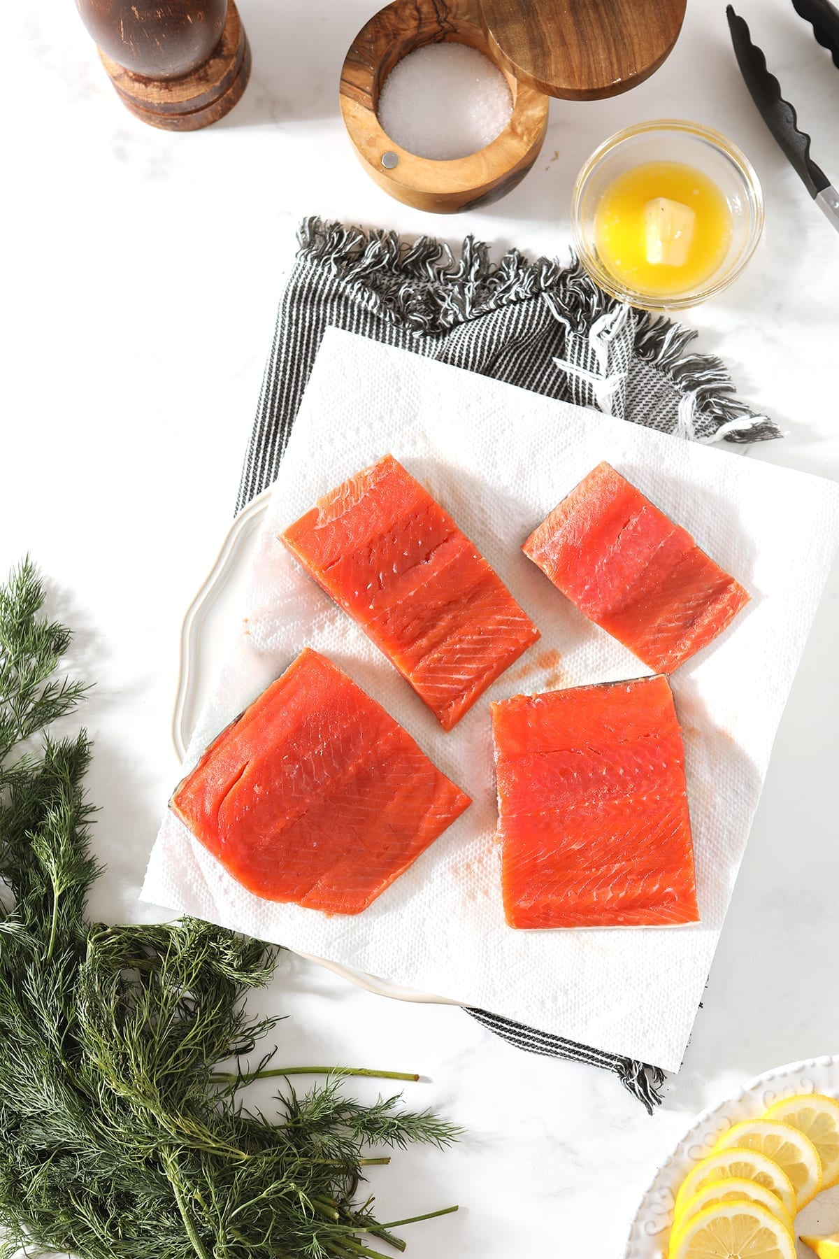 Salmon filets on a white plate lined with paper towels, surrounded by fresh dill, lemon rounds, melted butter and containers of salt and pepper