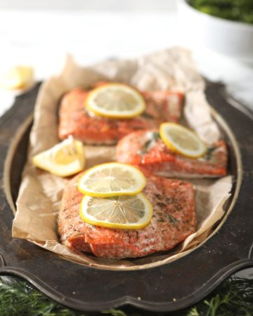 Three salmon filets on a metal platter on parchment paper, surrounded with fresh dill and garnished with lemon rounds