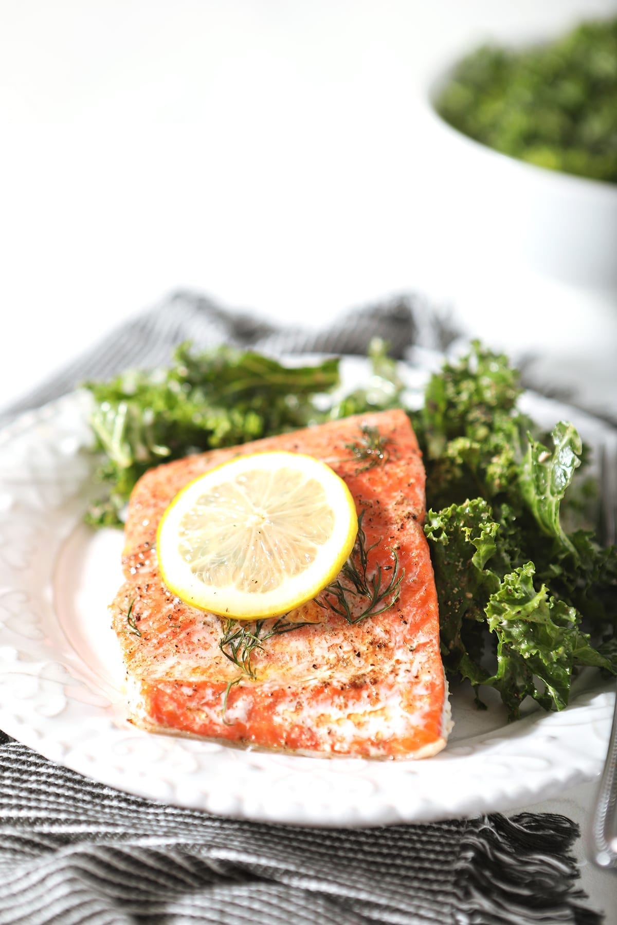 A baked salmon filet garnished with a lemon round and served with a kale salad on a white plate