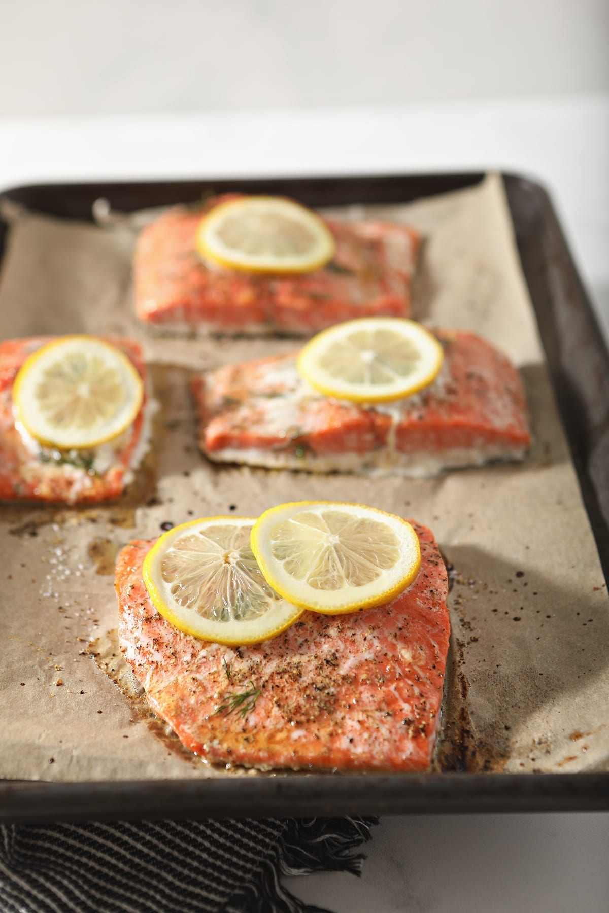 Four salmon filets sit on a baking sheet, garnished with lemon rounds, over a dark grey and white striped towel