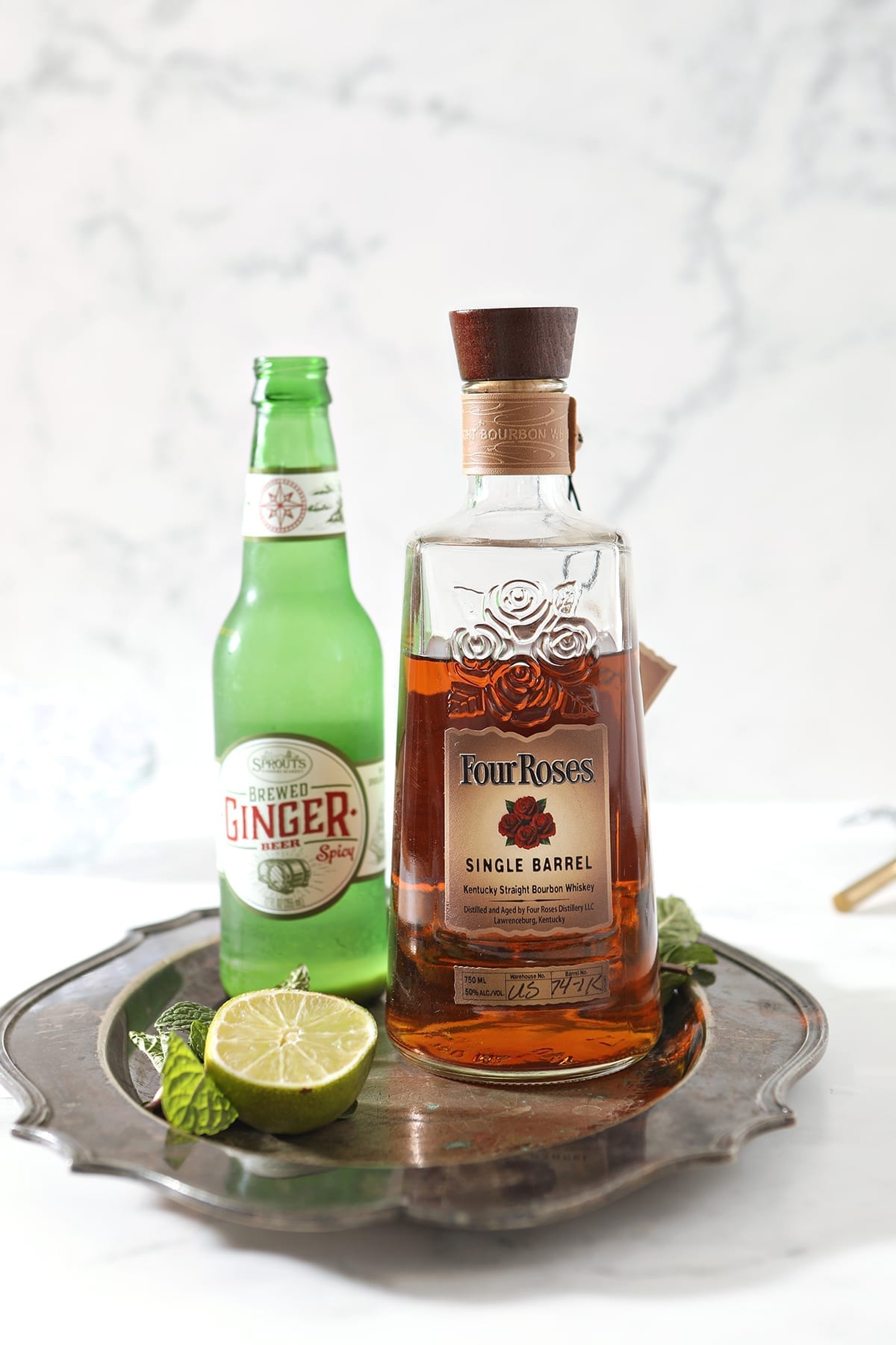A bottle of bourbon, ginger beer and a lime with mint are shown on a silver platter