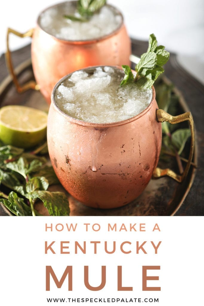 A silver platter holds two copper mugs holding Kentucky Bourbon Mules, with Pinterest text