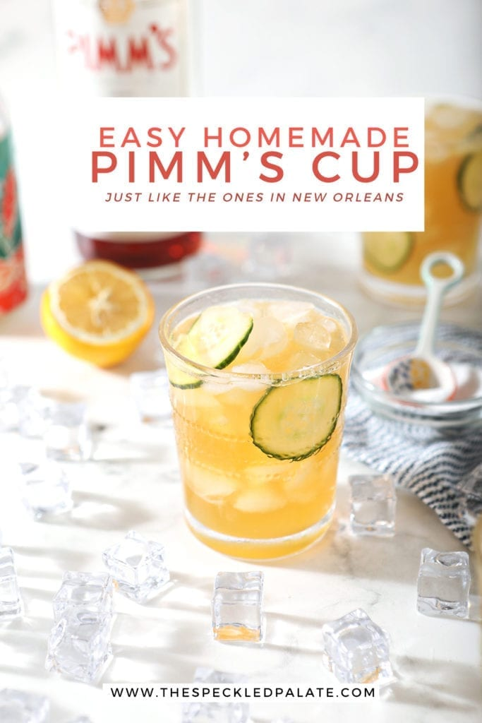 Two Pimm's Cups are surrounded by ingredients and ice, from a 45 degree angle, on marble, with Pinterest text
