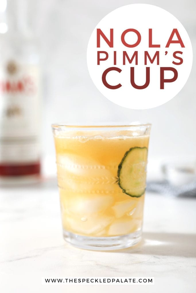 A Pimm's Cup, surrounded by ice and ingredients, is served on a marble surface, with Pinterest text