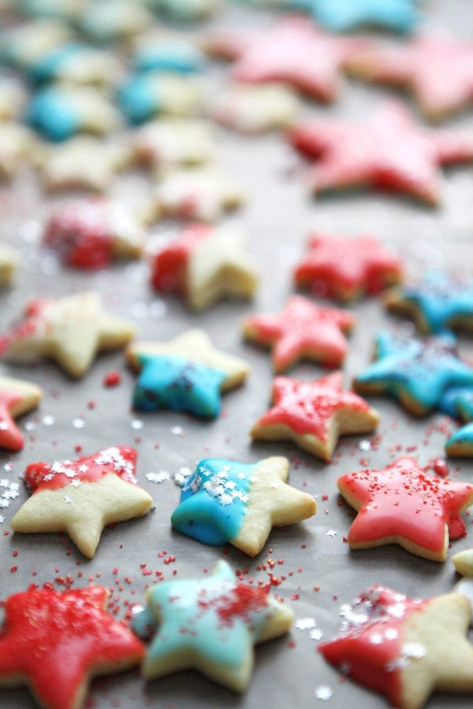 Star-shaped cookies on wax paper, after icing and sprinkles are added