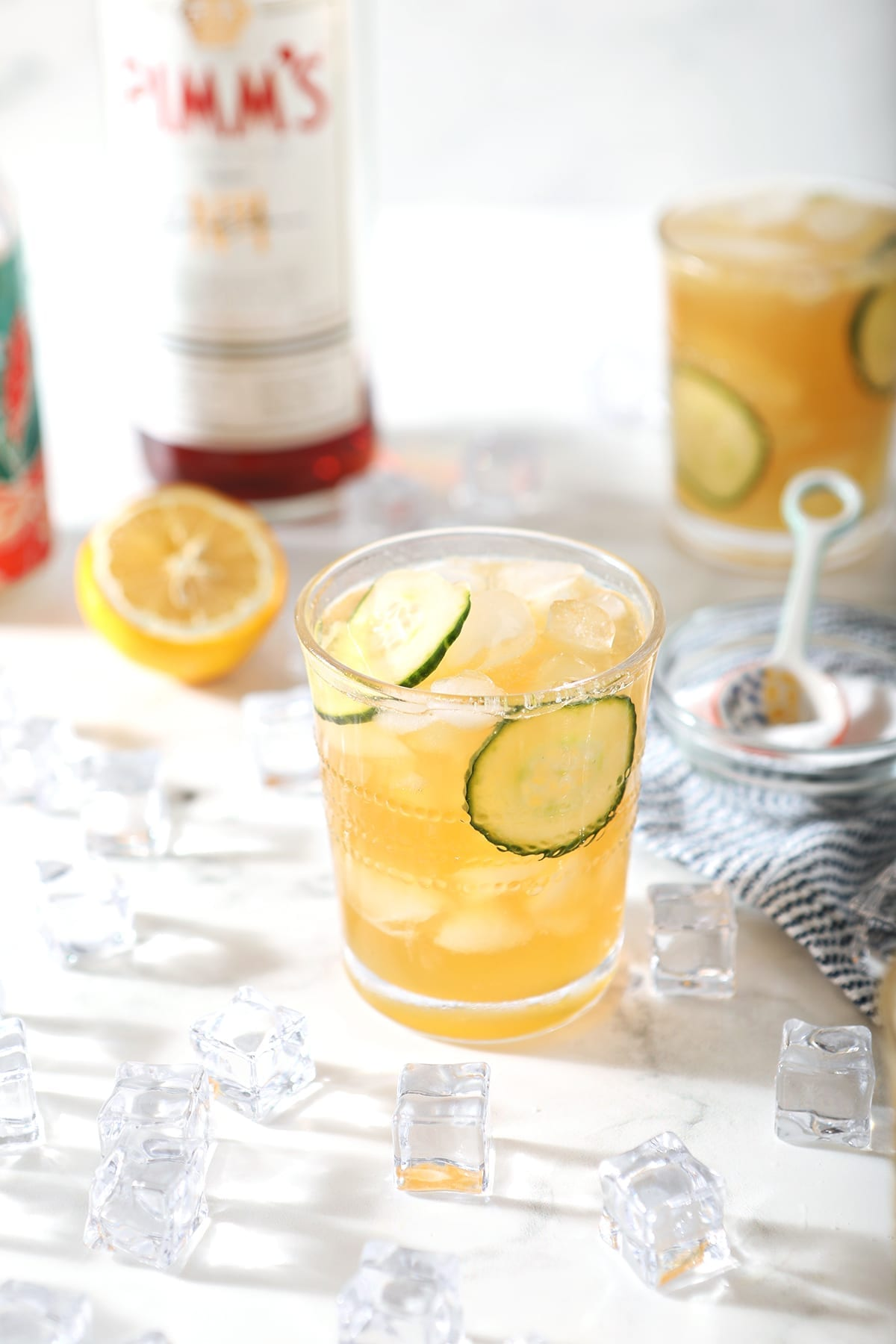 Two Pimm's Cups are surrounded by ingredients and ice, from a 45 degree angle, on marble