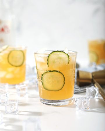 A Pimm's Cup, surrounded by ice and ingredients, is served on a marble surface