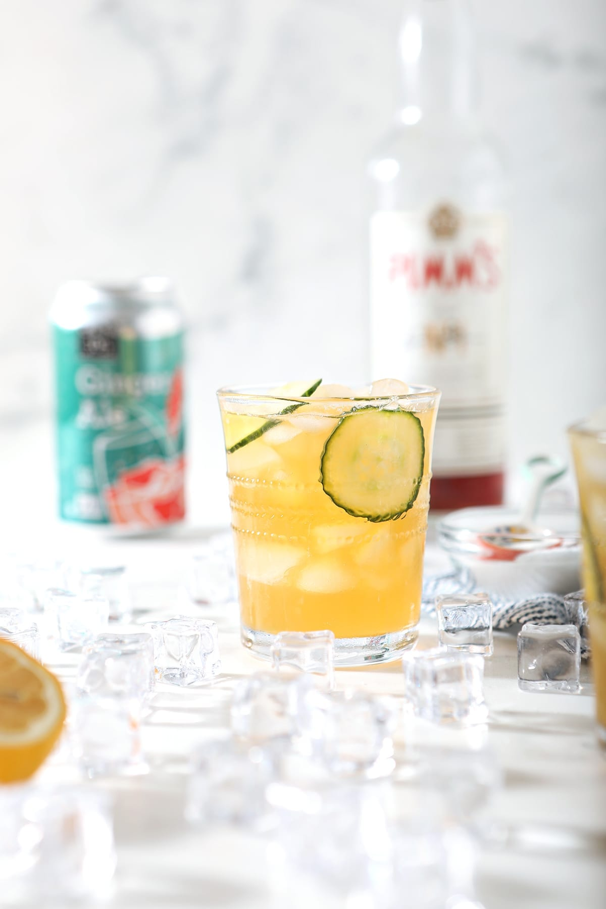 A Pimm's Cup sits in front of ingredients for the drink and ice