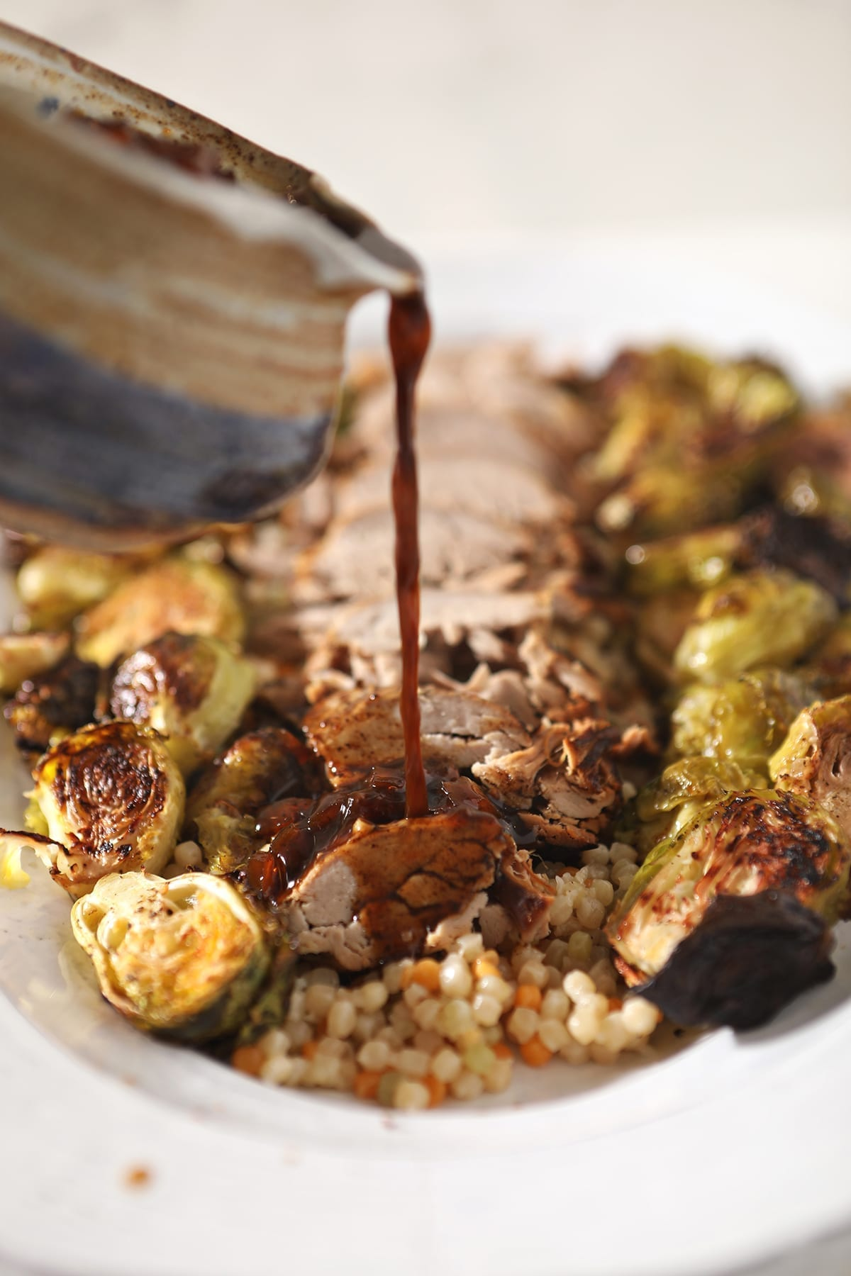 A sauce pours into a sliced pork tenderloin on a white platter with roasted brussels sprouts