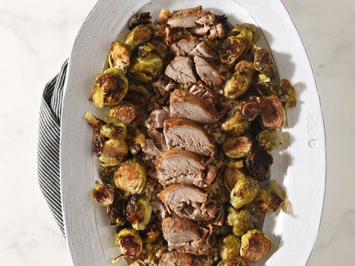 Sliced pork tenderloin and brussels sprouts on a large white platter