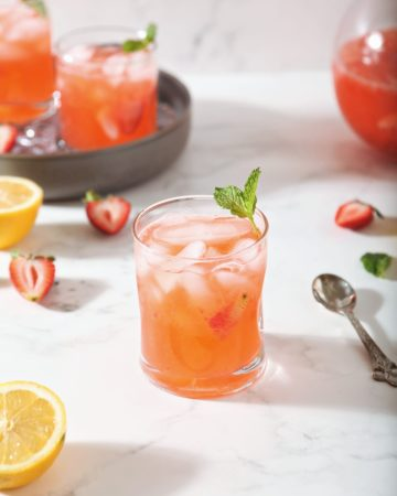 A glass of Strawberry Lemonade is shown with fresh strawberries and lemon slices