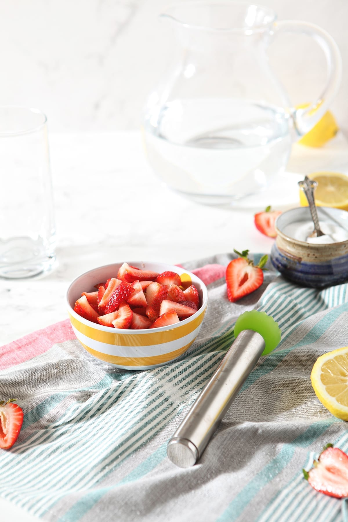 A bowl of strawberries, a pitcher of water and lemons are shown on marble