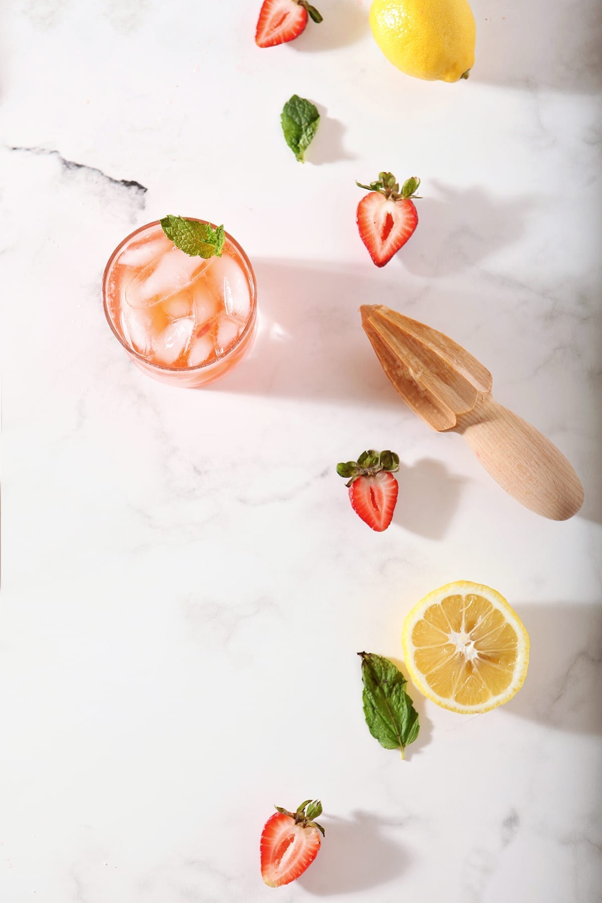 A glass of Strawberry Lemonade with its ingredients on a marble counter