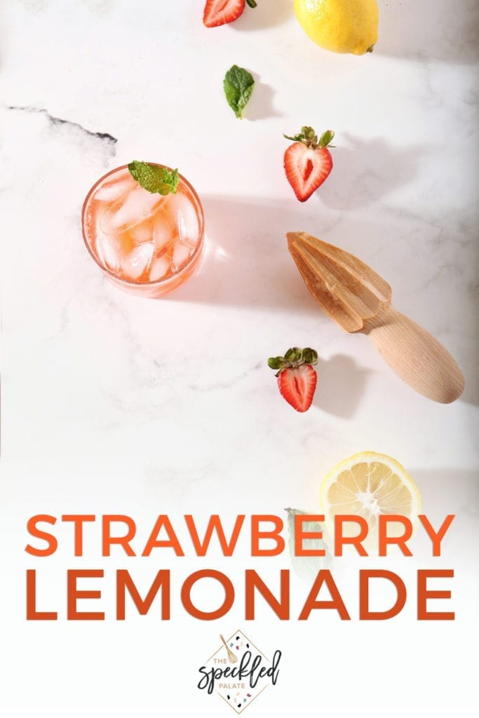 A glass of Strawberry Lemonade with its ingredients on a marble counter with text