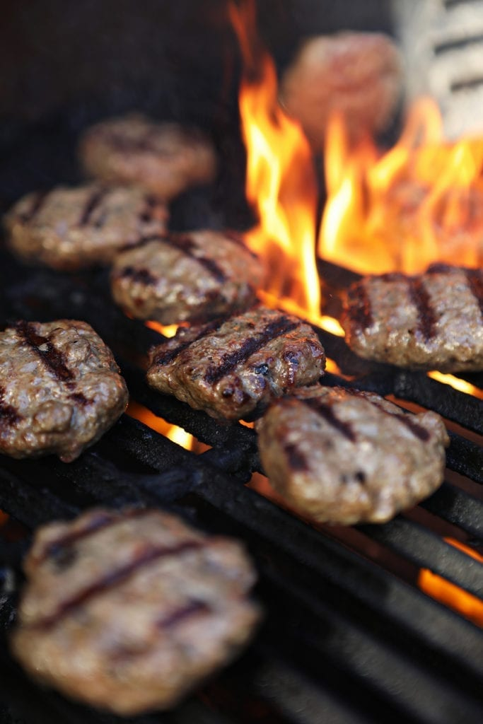 A spatula flips a beef slider on the grill as a flame flares up