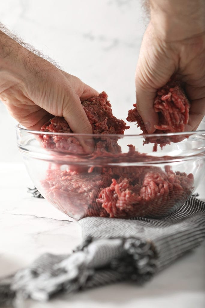 A man mixes ground beef with seasonings in a bowl with his hands