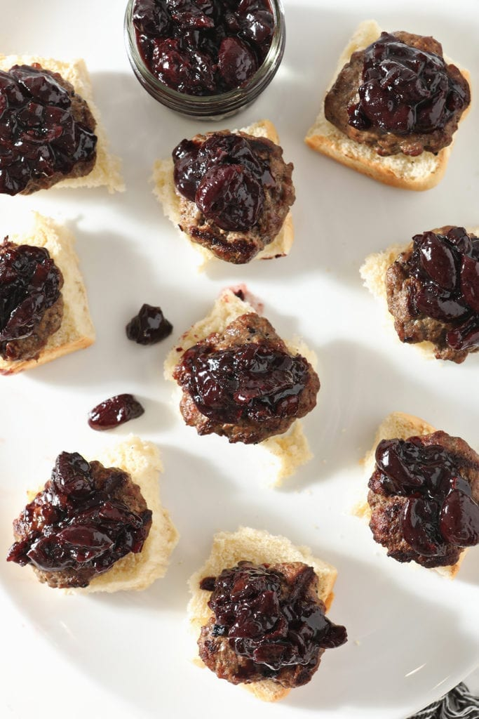 Beef sliders topped with cherry compote sit on a white platter before the tops of the buns are added