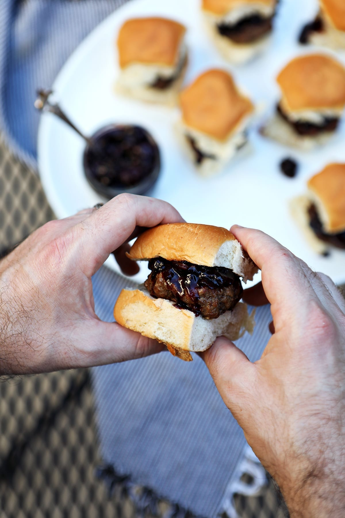 A man holds a slider between his hands with a white platter of other sliders in the background