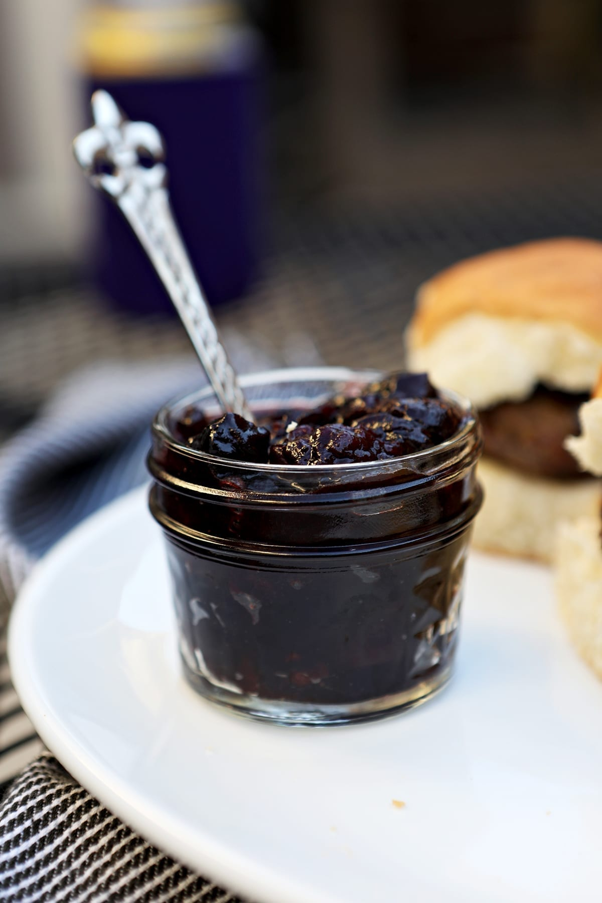 A small jar of compote sits on a white platter next to sliders