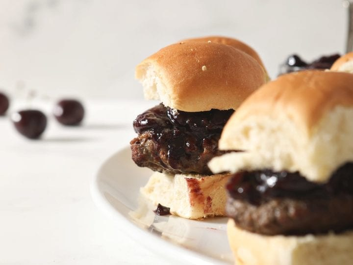 Hamburger sliders with Bacon Cherry Compote sit on a white platter before serving