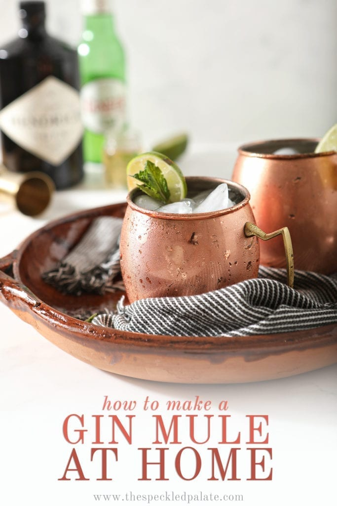 "Two copper mugs garnished with lime rounds and mint are shown in a brown serving tray holding Gin Gin Mules, with text stating ""How to Make a Gin Mule at Home"""