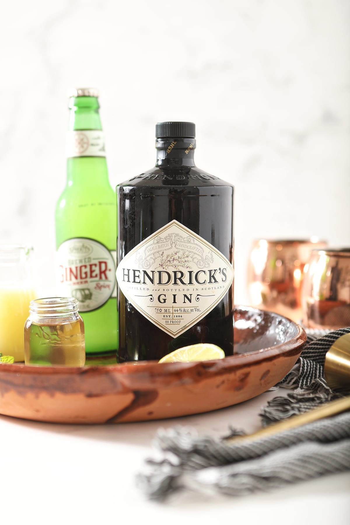 A bottle of Hendrick's gin sits with a bottle of ginger beer, lime juice and simple syrup in a brown serving platter